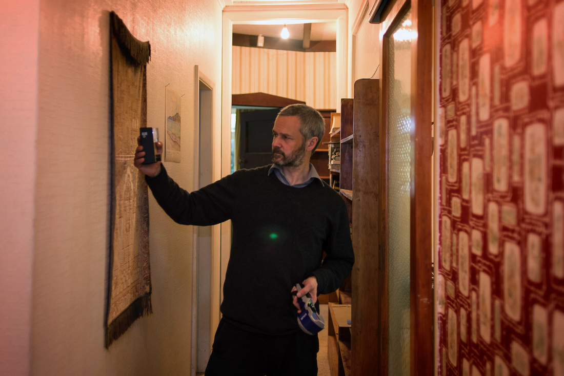 James Gilberd of the New Zealand Strange Occurrences Society investigates a private residence using a Trifield EMF meter and a FLIR heat camera. The green orb is probably caused by lens flare from the light bulb, paranormal investigation in New Zealand